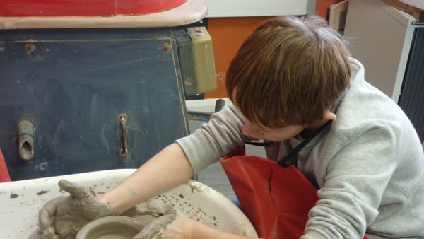 One of JACs young participants deep in concentration throwing a pot.